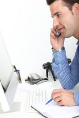 Junger Mann telefoniert im Büro