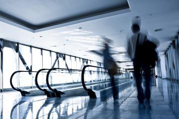 People move in glass corridor