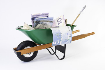 Green wheel barrel full of dollars bills