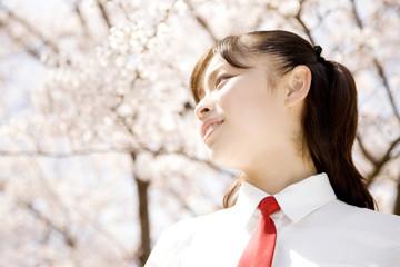 桜の下で微笑む女子高生