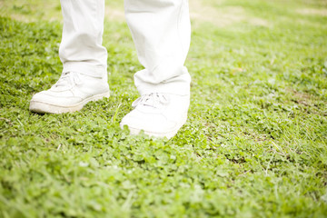 芝生の上に立つ男性の足元