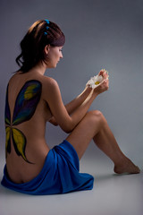 beautiful girl with bodyart sitting and looking at the flower