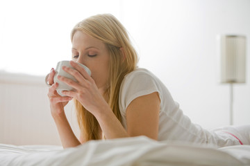Woman in Bed With Coffee Cup