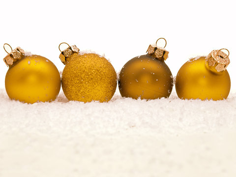 vier goldene Weihnachtskugeln, die auf dem Schnee liegen