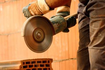 Worker cutting bricks