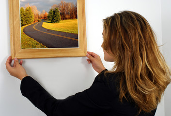 young woman fixing a picture frame on the wall