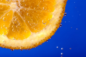 Slice of an orange plunged in soda water