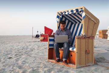 Geschäftsmann bei der Arbeit am Strand mit Laptop