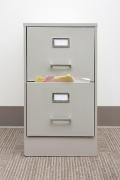 Detail of a full filing cabinet with blank drawer labels.