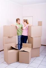joyful couple standing in between unopened boxes