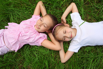 Two girls lie on grass with closed eyes,  head to head