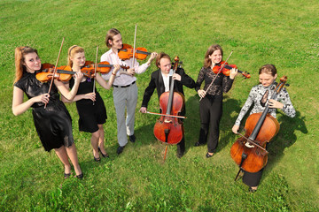 Six violinists stand semicircle on  grass and play