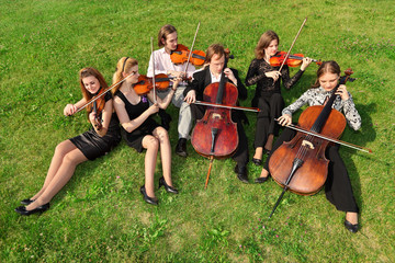 Six violinists sit semicircle on  grass and play