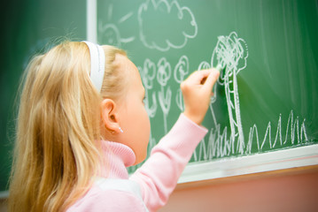 little girl drawing on school board