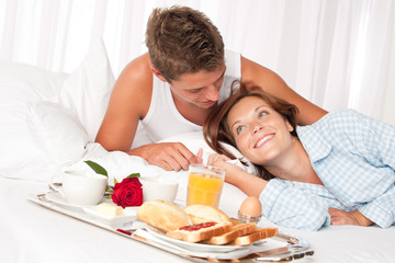 Young smiling couple having luxury breakfast in hotel room
