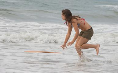 Teen girl skim boarding at the beach.