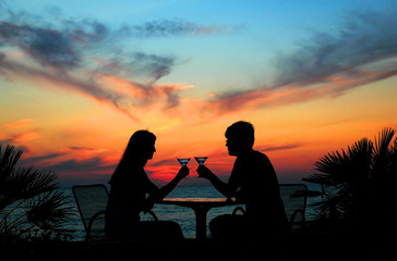 The pair silhouette is held by goblet on a sundown