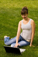 Young woman with notebook on the grass