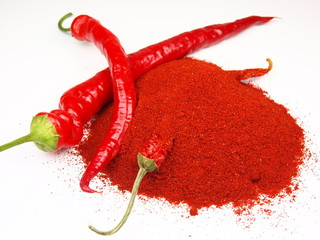 Red chilli pepper with pile of milled spice on white background