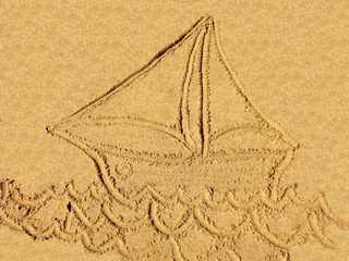 golden sail boat drawn on the sand