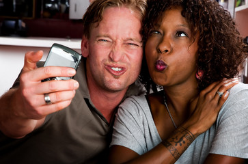 Mixed race couple in coffee house with taking picture cell phone