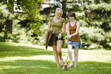 Women walking dog at a park