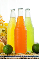 Three cold drinks in glass bottles with limes next to them