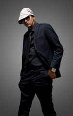 studio shot of a young man wearing black suit and sunglasses
