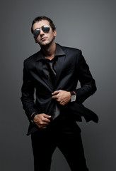 attractive young man wearing elegant black suit and sunglasses