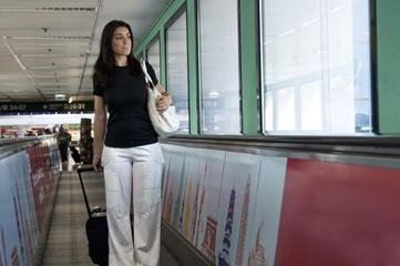 Mulher na esteira do aeroporto com sua bagagem