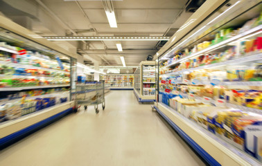 blurred supermarket shelves and aisle with trolley