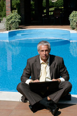 Angry businessman sitting next to swimming pool