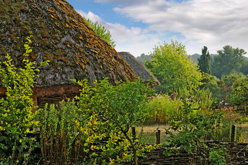 Vivid scenic ancient rural landscape with straw roofs