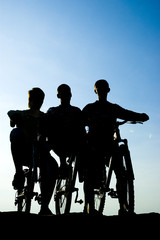 Silhouette of the bikers and bicycle on sky background.