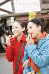観光地でまんじゅうを食べる女性2人