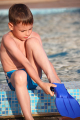 boy puts on flipperson border of pool