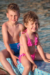 boy and girl sit on border of pool