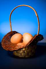 Hand basket with fresh eggs , blue background