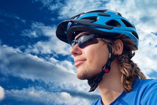 portrait of a young bicyclist in helmet and glasses