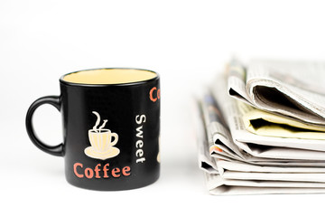 Coffee cup and stack of newspapers