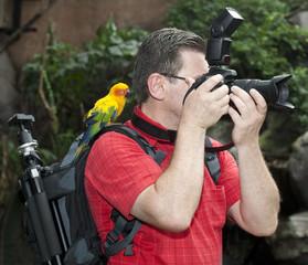 Fotograf mit Vogel auf der Schulter