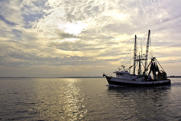 Fishing trawler on the water at sunrise