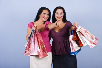 Woman pointing and holding shopping bags