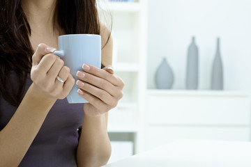 Female hands holding tea cup