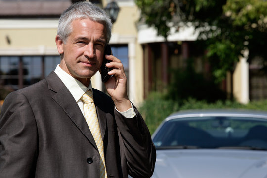 Portrait of handsome mature businessman on cell phone