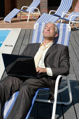 Businessman with laptop computer resting on deck chair