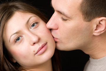 Man kisses young woman in cheek.