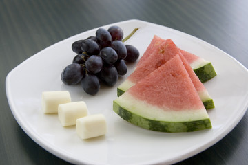 A plate of fresh fruit and cheese.