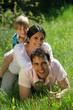 homme et femme avec un petit garçon couchés dans l'herbe