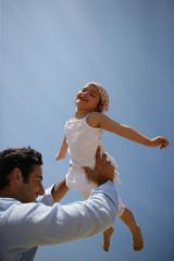 Homme soulevant une petite fille dans ses bras